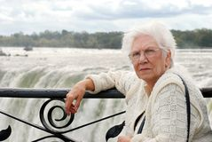 Senior woman sitting at edge of niagara falls. Beautiful portrait of a senior woman sitting at edge of niagara falls royalty free stock images