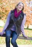 Senior woman sitting on fence Stock Photos
