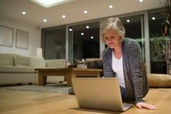 Senior woman sitting on the floor working on laptop Stock Photos
