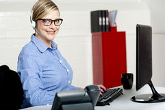 Senior woman sitting in front of computer Stock Photo