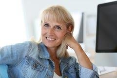 Senior woman sitting in front of desktop computer Stock Image