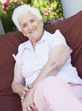 Senior woman sitting on garden chair Royalty Free Stock Photos