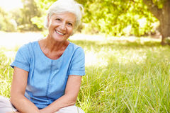 Senior woman sitting on grass relaxing Royalty Free Stock Photo