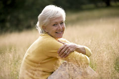 A senior woman sitting on the grass, smiling Stock Photography
