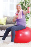 Senior woman sitting on gym ball, and exercise with weights at h Royalty Free Stock Image