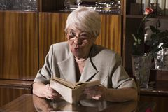 Senior woman sitting at home. Royalty Free Stock Images