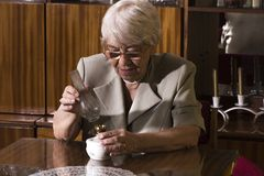Senior woman sitting at home. Happy senior woman sitting at home and relaxing Royalty Free Stock Images