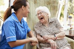 Free Senior Woman Sitting In Chair And Laughing With Nurse In Retirement Home Stock Images - 134203074