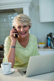 Senior woman sitting with laptop and talking on mobile phone Stock Images
