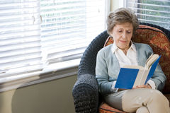 Senior woman sitting on living room chair reading royalty free stock photography