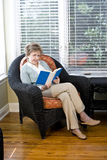 Senior woman sitting on living room chair reading. Book Stock Images