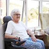Senior Woman Sitting In Lounge Of Retirement Home In Motorized Wheelchair royalty free stock photo