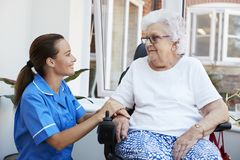 Senior Woman Sitting In Motorized Wheelchair Talking With Nurse In Retirement Home royalty free stock images