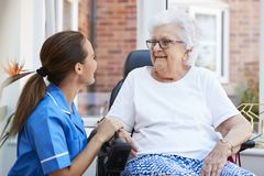 Senior Woman Sitting In Motorized Wheelchair Talking With Nurse In Retirement Home royalty free stock photo