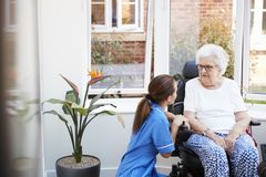 Senior Woman Sitting In Motorized Wheelchair Talking With Nurse In Retirement Home royalty free stock photography