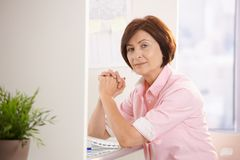 Senior woman sitting at office desk Royalty Free Stock Image