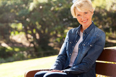 Senior woman sitting outdoors Stock Image