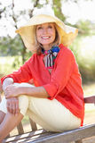 Senior Woman Sitting Outdoors On Bench. Smiling To Camera Royalty Free Stock Image