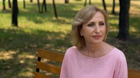 Senior woman sitting in park, enjoying retirement leisure, waiting for man royalty free stock photography