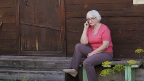 Senior woman sitting on porch of home calling to mobile phone in countryside. Elderly woman using smart phone for call in garden stock footage