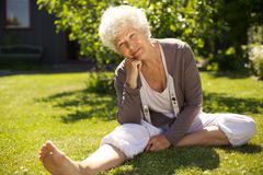 Senior woman sitting relaxed in backyard Stock Image