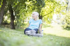 Senior woman sitting and resting after workout in park on grass royalty free stock photography