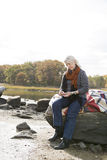 Senior woman sitting on rocks Stock Images