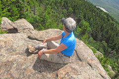 Senior Woman sitting on rocks. Senior woman sitting on mountain summit overlooking view down mountainside Stock Images