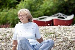 Senior woman sitting on rocky beach Royalty Free Stock Photo
