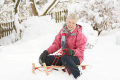 Senior Woman Sitting On Sledge In Snowy Landscape. Smiling at camera Stock Photo