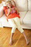 Senior Woman Sitting On Sofa Reading Diary Royalty Free Stock Image