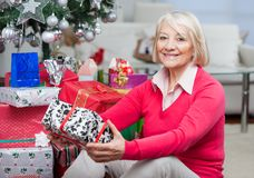 Senior Woman Sitting By Stack Of Christmas Stock Image