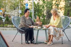 Senior woman sitting in street cafe, drinking coffee, talking, laughing and having fun. Happy people in retirement. Senior women sitting in street cafe, drinking Stock Image