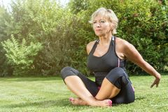 Senior woman is sitting in a stretched pose outdoors. Attractive senior blond woman is sitting in a stretched pose with her breasts outstretched and her hands in Royalty Free Stock Images