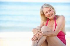 Senior Woman Sitting On Summer Beach Stock Photos