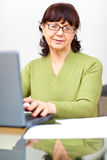 Senior woman sitting at the table with computer Royalty Free Stock Image