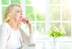 Senior woman with cup of tea. Senior woman sitting at table with cup of tea Stock Photos