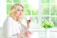Senior woman with cup of tea. Senior woman sitting at table with cup of tea Royalty Free Stock Photography