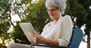 Senior woman sitting with tablet at the park Royalty Free Stock Image