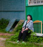 A senior woman sitting tired near her house in the village stock image