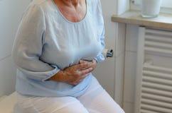Senior woman sitting on toilet Royalty Free Stock Image