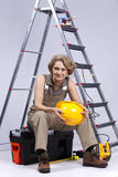 Senior woman sitting in a toolbox Stock Photo