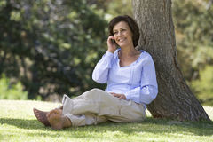 A senior woman sitting under a tree using a mobile telephone Royalty Free Stock Image