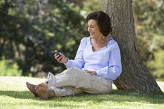 A senior woman sitting under a tree using a mobile telephone Royalty Free Stock Images