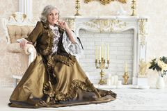 Senior woman sitting in vintage chair. Beautiful senior woman in dress sitting in vintage chair near fireplace Royalty Free Stock Photography