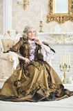 Senior woman sitting in vintage chair. Beautiful senior woman in dress sitting in vintage chair near fireplace Royalty Free Stock Images