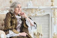 Senior woman sitting in vintage chair. Beautiful senior woman in dress sitting in vintage chair near fireplace Royalty Free Stock Image