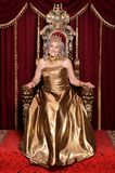 Senior woman sitting in vintage chair. Beautiful senior woman in golden dress with crown sitting in vintage chair Stock Photography