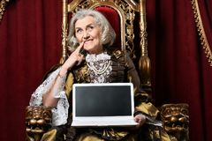 Senior woman sitting in vintage chair. Beautiful senior woman in golden dress sitting in vintage chair with laptop on her knees Stock Photos
