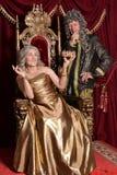 Senior woman sitting in vintage chair. Beautiful senior women in golden dress with crown sitting in vintage chair with chevalier nearby Stock Photography